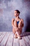 La bailarina joven que se sienta en el piso de madera Fotos de archivo