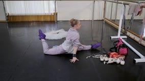 La bailarina que hace diligente estirar, calienta en una clase del ballet El bailarín de ballet en traje rosado practica en gimna almacen de metraje de vídeo