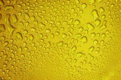 La baisse abstraite de l'eau sur la surface du fond jaune frais photo stock