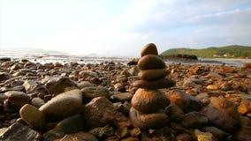 la balanza y la armonía de la pila de la roca 4K en el mar varan con la igualación de la luz y del sonido ambiente metrajes
