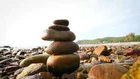 la balanza y la armonía de la pila de la roca 4K en el mar varan con la igualación de la luz y del sonido ambiente almacen de video