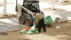 La balayeuse prend des sacs de déchets photos stock