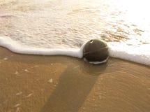 La balise sur la plage et frappée les vagues Photos stock