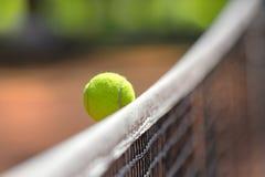 La balle de tennis au-dessus du filet tombe dans le domaine opposé du ` s Photographie stock libre de droits
