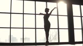 La ballerina elegante sta filando sulle punte dei piedi in scarpe del pointe Siluetta del ballerino di balletto nello studio cont video d archivio
