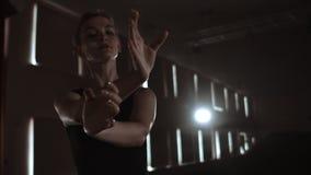 La ballerina graziosa della donna in un vestito scuro su una fase scura del teatro nel fumo realizza i movimenti di ballo al rall archivi video