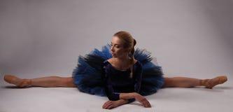La ballerina nella manifestazione blu dell'attrezzatura ha spaccato sul pavimento dello studio Fotografia Stock
