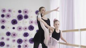 La ballerina professionista dell'insegnante di balletto sta insegnando ai movimenti ed alle curvature della gamba della ragazza a video d archivio