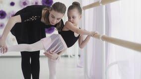 La ballerina professionista dell'insegnante di balletto sta insegnando ai movimenti ed alle curvature della gamba della ragazza a stock footage