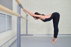 La ballerina si allunga vicino alla sbarra nell'aula, bello allungamento delle donne Fotografie Stock