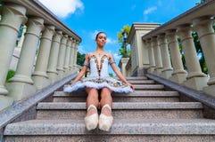 La ballerina si siede sulle scale, stanti nella posizione del pointe All'aperto, molla Fotografia Stock