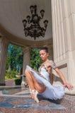 La ballerina si siede vicino alla colonna, stante nel pointe Immagine Stock