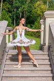 La ballerina sta sulle scale, stanti nella posizione del pointe All'aperto, molla Immagini Stock