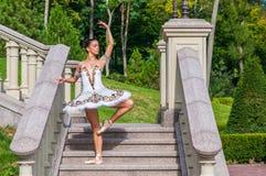 La ballerina sta sulle scale, stanti nella posizione del pointe All'aperto, molla Immagine Stock Libera da Diritti