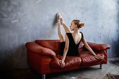 La ballerine mince superbe dans une robe noire pose dans le studio photos stock