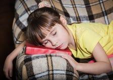 La bambina è caduto addormentato con un libro nell'ambito della sua testa Fotografia Stock Libera da Diritti