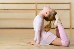 La bambina è occupata esercitarsi sul pavimento Fotografia Stock Libera da Diritti