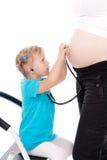 La bambina è pancia incinta d'ascolto Immagine Stock Libera da Diritti
