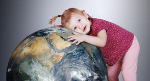 La bambina abbraccia delicatamente il globo della terra Fotografie Stock Libere da Diritti