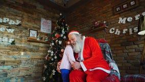 La bambina abbraccia Santa Claus e fa il desiderio per il Natale nella stanza decorata accogliente per holidayn stock footage