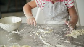La bambina abilmente fa fronte nella cucina vuole aiutare i suoi genitori nella cottura stock footage