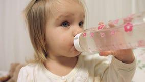La bambina adorabile beve l'acqua da una bottiglia Fotografia Stock