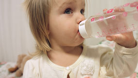 La bambina adorabile beve l'acqua da una bottiglia Immagine Stock