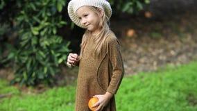 La bambina adorabile che seleziona le arance mature fresche in arancio soleggiato fa il giardinaggio in Italia archivi video