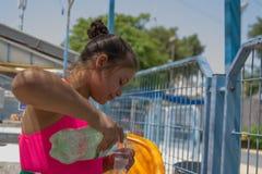 La bambina adorabile versa una bevanda vicino allo stagno di acqua ragazza sveglia del ritratto in costume da bagno rosa vicino a Fotografia Stock Libera da Diritti