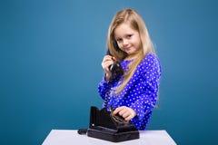 La bambina adorabile in vestito porpora tiene il microtelefono del telefono immagine stock