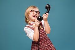 La bambina adorabile in vestito rosso, camicia bianca e vetri tiene il microtelefono del telefono immagine stock