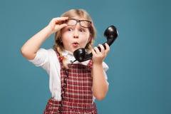 La bambina adorabile in vestito rosso, camicia bianca e vetri tiene il microtelefono del telefono immagine stock libera da diritti
