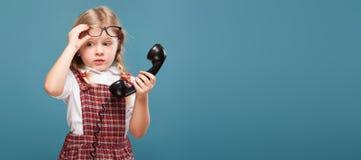 La bambina adorabile in vestito rosso, camicia bianca e vetri tiene il microtelefono del telefono immagini stock