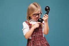 La bambina adorabile in vestito rosso, camicia bianca e vetri tiene il microtelefono del telefono fotografie stock