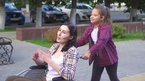 La bambina aiuta la madre ad un disabile in una sedia a rotelle sulla passeggiata Mo lento video d archivio