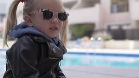 La bambina alla moda cammina nell'iarda alla spigola stock footage