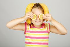 La bambina allegra con il limone e la banana posa positivamente dentro fotografia stock libera da diritti