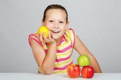 La bambina allegra con le mele ed il limone posa positivamente nella s immagini stock libere da diritti