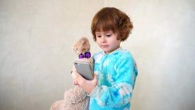 La bambina allegra fa i fronti sul telefono del ` s della madre Immagine Stock