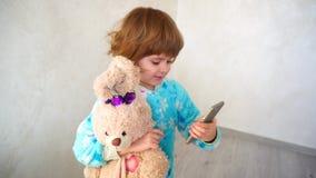 La bambina allegra fa i fronti sul telefono del ` s della madre Immagine Stock Libera da Diritti