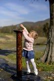 La bambina allunga le sue mani alla fontana fotografia stock libera da diritti