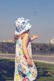 La bambina allunga le sue mani alle bolle Immagini Stock