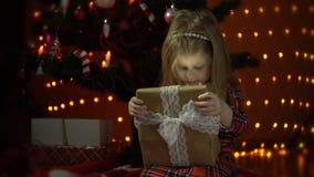 La bambina apre il contenitore di regalo sotto l'albero di Natale decorato video d archivio