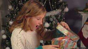 La bambina apre il regalo del ` s del nuovo anno stock footage