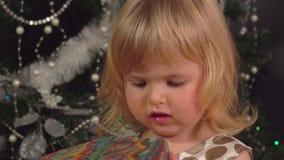 La bambina apre il regalo del ` s del nuovo anno video d archivio