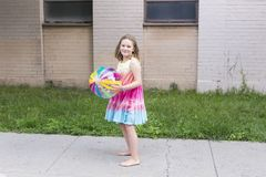 La bambina in arcobaleno ha colorato il vestito ed i piedi nudi che tengono il chiaro beach ball del vinile Fotografia Stock Libera da Diritti