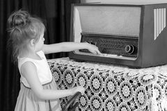 La bambina ascolta la vecchia radio Immagini Stock Libere da Diritti