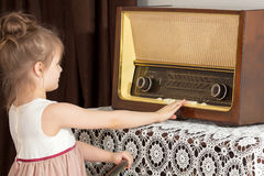 La bambina ascolta la vecchia radio Immagine Stock Libera da Diritti