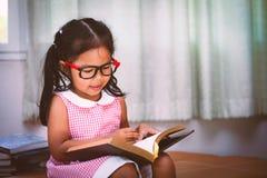 La bambina asiatica del bambino ha messo sopra gli occhiali che legge un libro Fotografia Stock