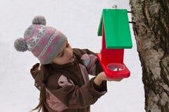 La bambina attacca l'alimentatore dell'uccello ad un albero Fotografia Stock